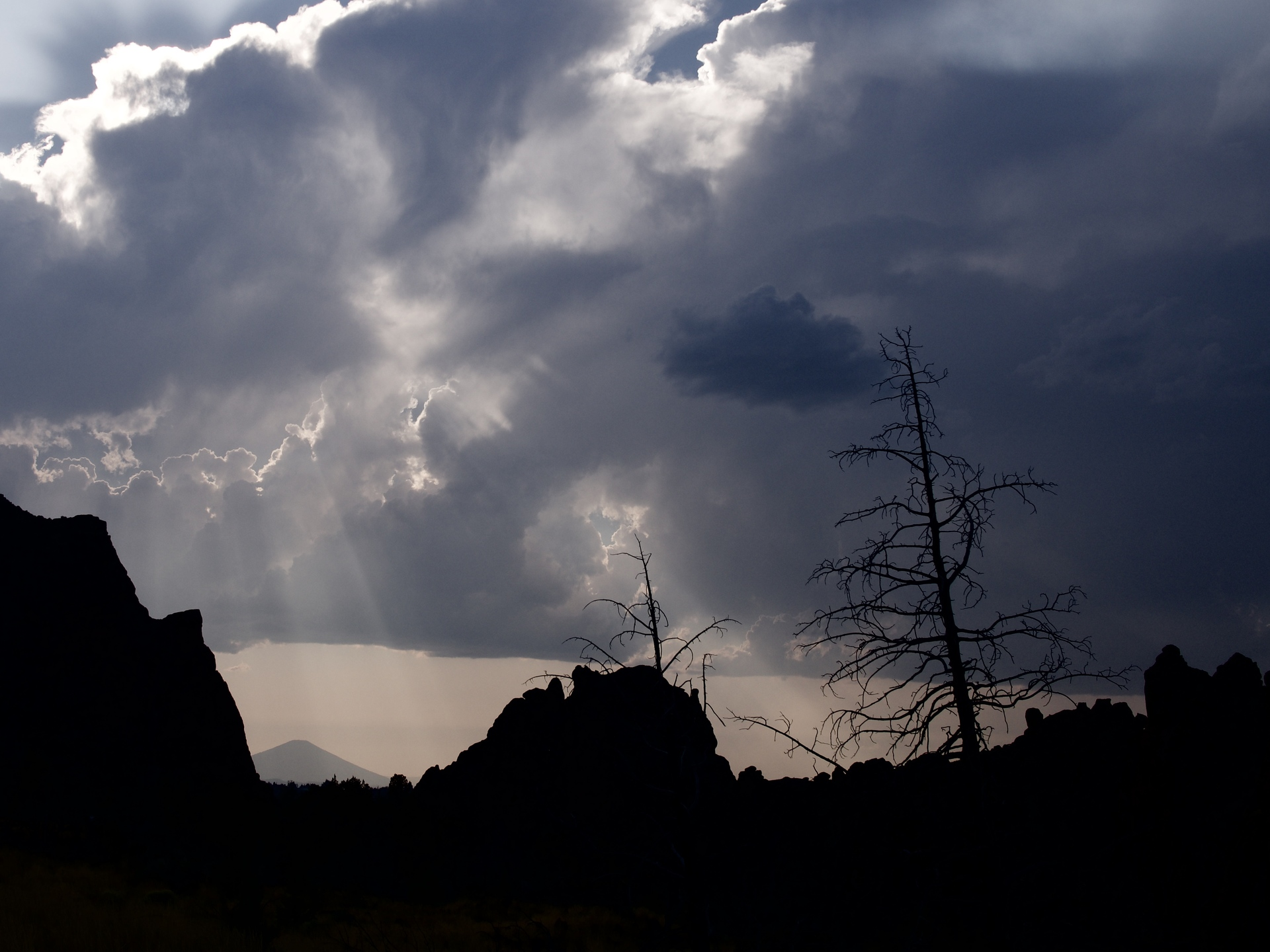 Beautiful sun rays break through the clouds after an evening summer rain storm at Smith Rocks in Central Oregon with Black Butte in the background and silhouetted trees in the foreground.