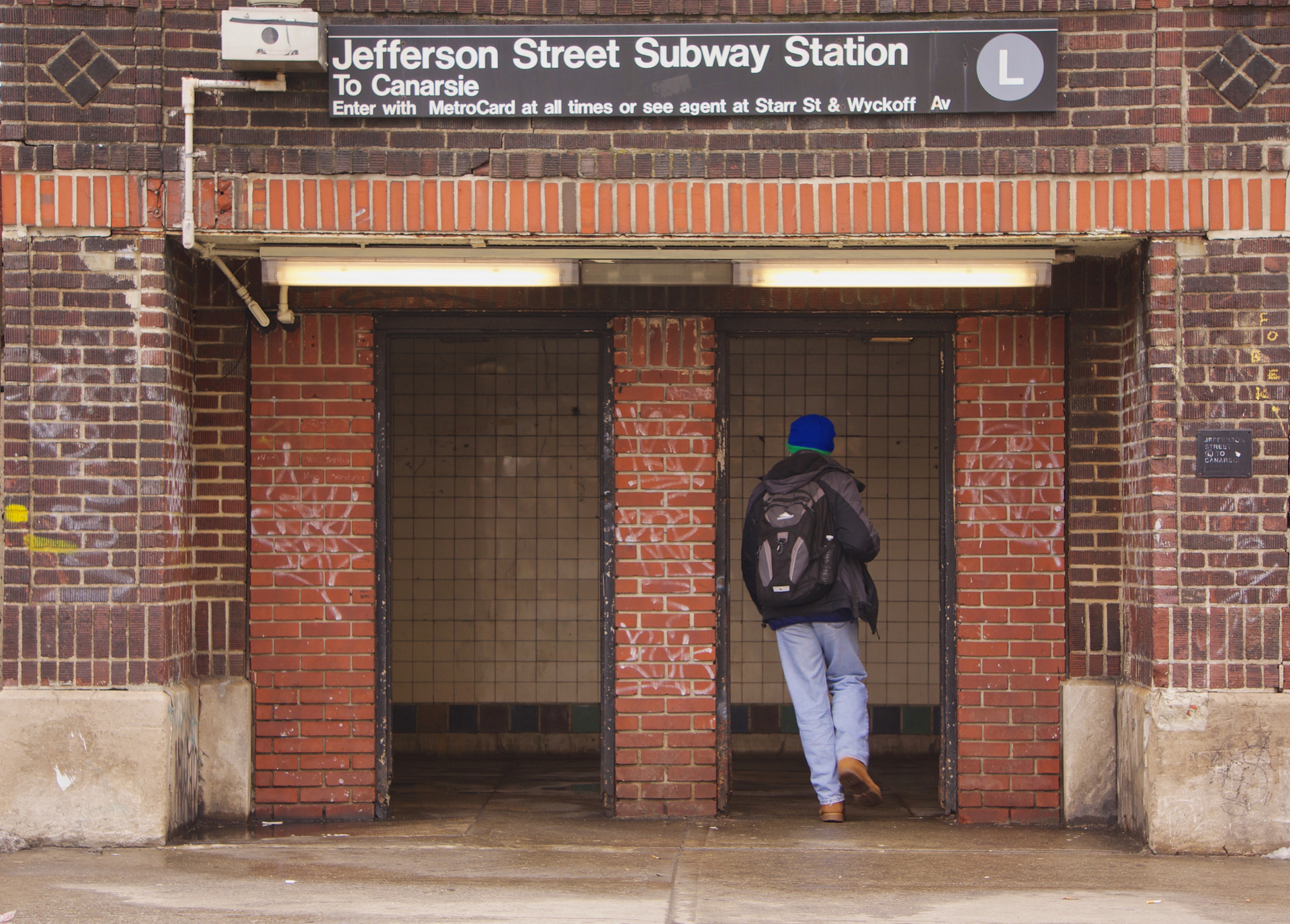 A man is running through an entrance door to an underground  New York Subway train.in Bushwick, Brooklyn, NYC