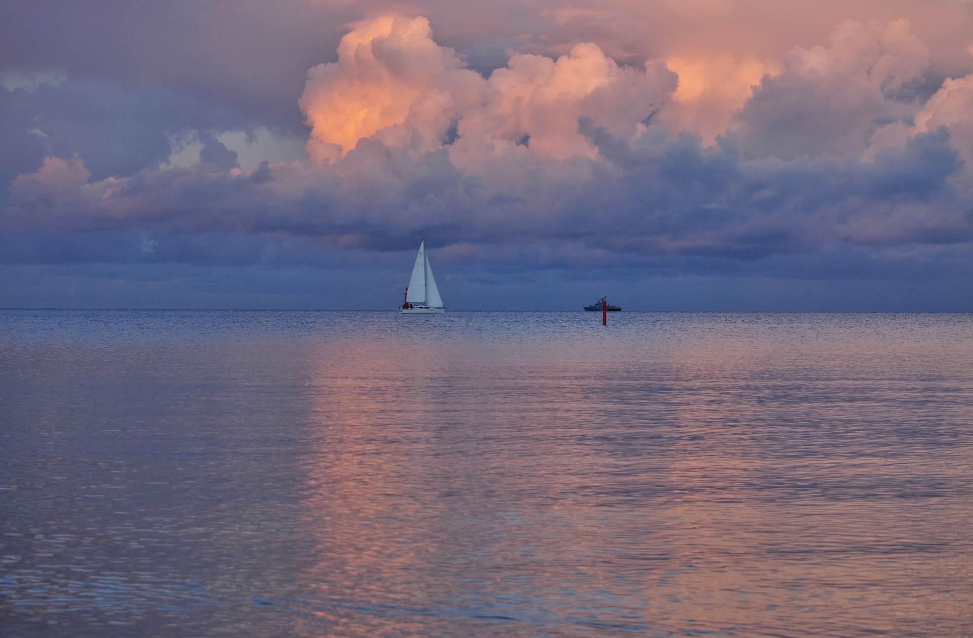 white sailboat on the dramatic sky background during august sunset at the baltic sea in poland