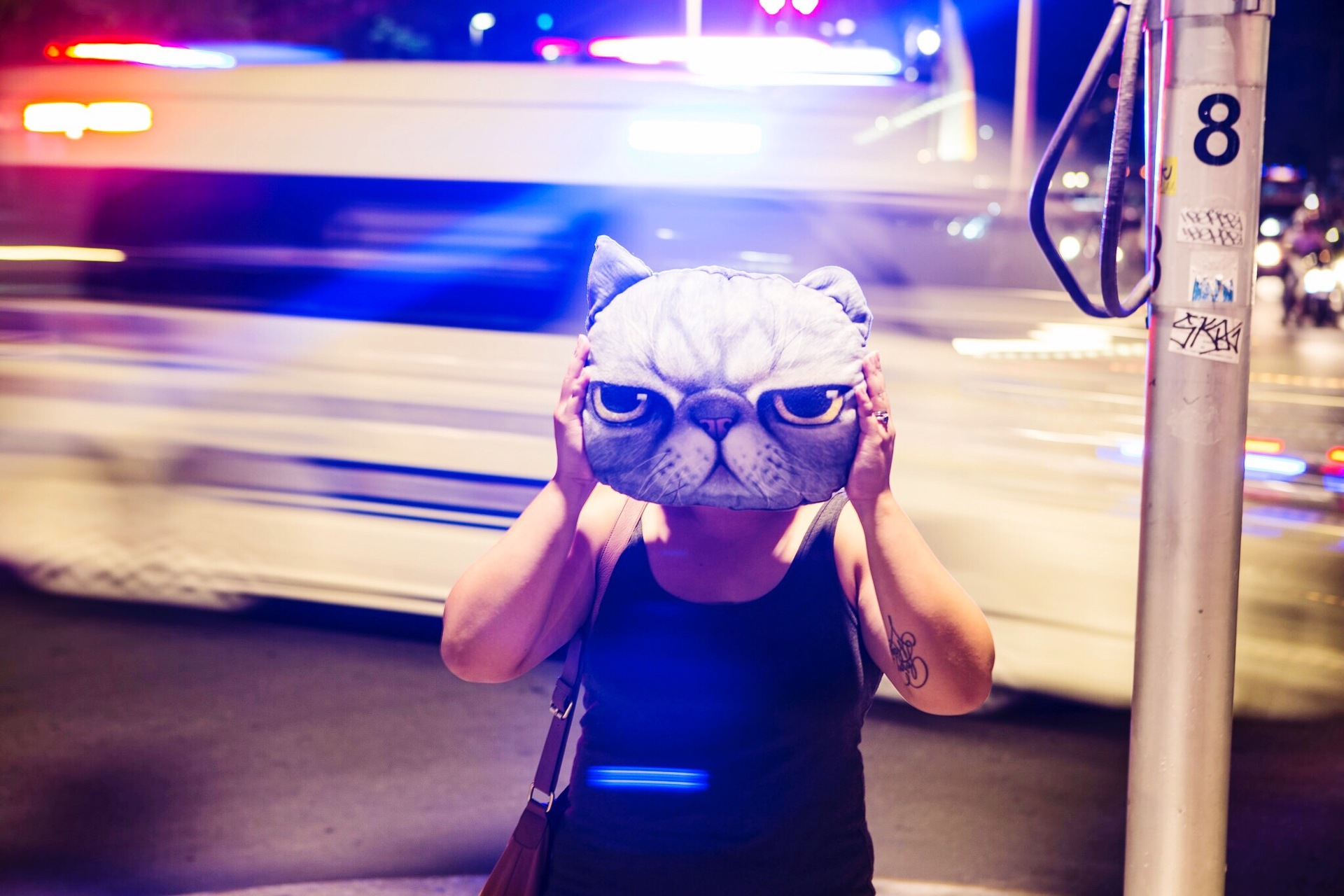 A tattooed woman holding a cat pillow. Bright city lights in the background. Cool urban scene